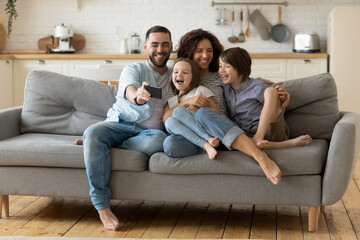 Smiling parents with little kids laughing using smartphone together sitting on couch at home. Happy...