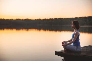 Woman exercising yoga pose vital and meditation for fitness lifestyle outside. sunrise on lake. nature background. Healthy and Yoga Concept. Peaceful lifestyle. copy space