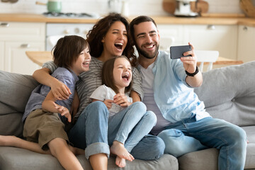 Close up happy parents with little children using smartphone together sitting on couch at home. Smiling father holding phone taking selfie with kids. Family watching video having fun with cellphone.