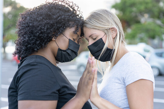 African and caucasian northern women together and wearing protective face masks - Black lives matter concept - Girlfriends, love and fight for human right