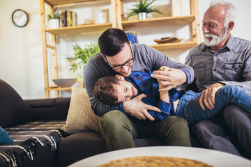 Three generations of men sit on couch having fun
