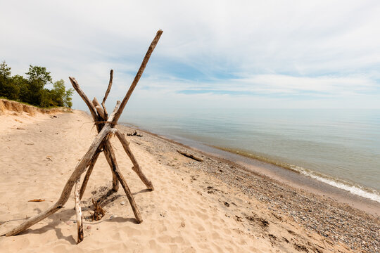 Driftwood is stacked along the beach at Kohler Andrae State Park, Sheboygan, Wisconsin as Lake Michigan is quite calm in mid-June