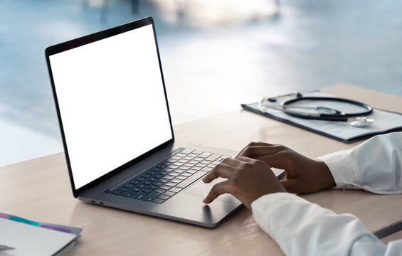 African american doctor wear white coat typing using laptop computer mock up white screen browsing internet sitting at work desk. Healthcare medical e health website technology concept. Close up view