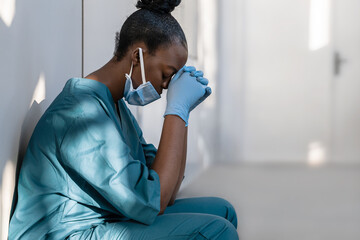 Tired depressed female african scrub nurse wears face mask blue uniform gloves sits on hospital...