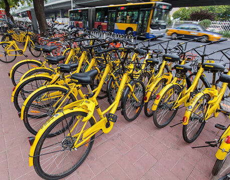 BEIJING, CHINA-JULY 2, 2017: A row of parked Ofo bicycles. Ofo, a bike-sharing company founded in 2014, has over 20 million registered users