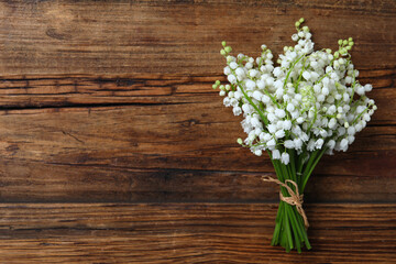 Beautiful lily of the valley flowers on wooden table, top view. Space for text
