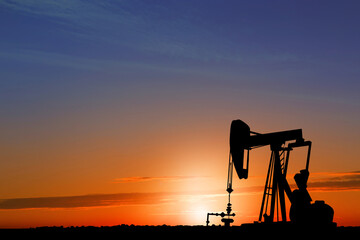 Silhouette of crude oil pump at sunset. Space for text