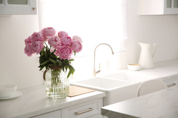 Vase with bouquet of beautiful pink peonies in kitchen. Space for text