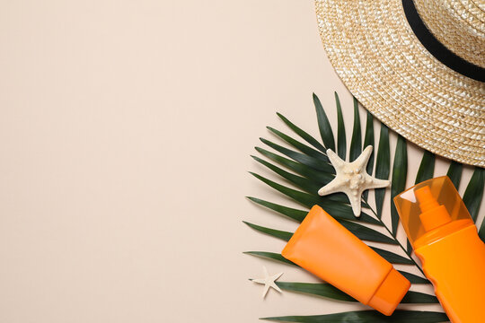 Flat lay composition with sun protection products and hat on beige background. Space for text