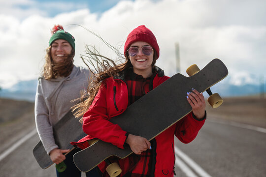 Two cheerful girls with long boards at the road