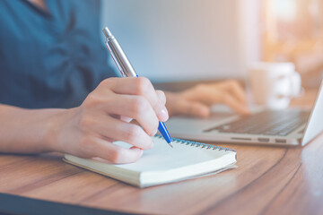 Woman is writing on a notebook with a pen and using a laptop to work in the office.