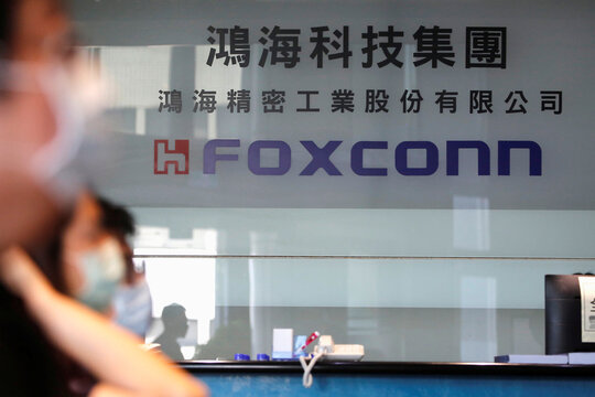 People wear masks to protect themselves from coronavirus disease (COVID-19), while listening to the annual general meeting at the lobby of Foxconn's office in Taipei