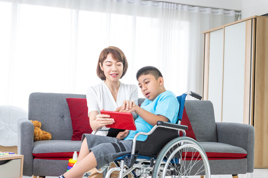 asian woman playing with disabled child on wheelchair by tablet in living room.