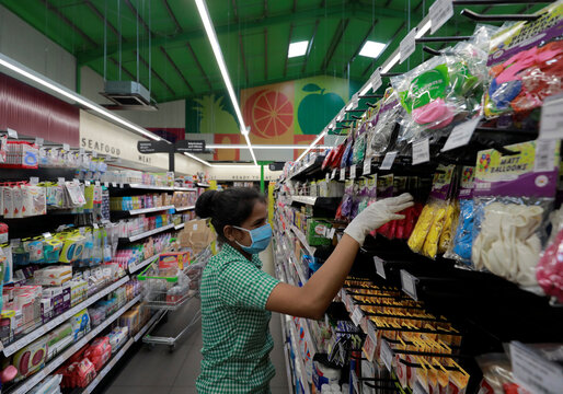 A staff official wearing protective mask checks the display tems quantity on a shelf at a Keels super market,amid concerns about the spread of the coronavirus disease, in Colombo