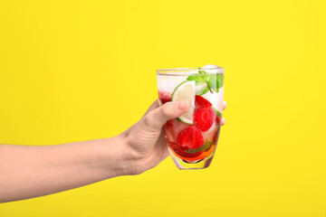 Hand with glass of fresh strawberry lemonade on color background