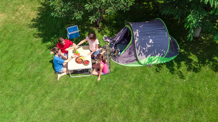 Family vacation in campsite aerial top view from above, parents and kids relax and have fun in park, tent and camping equipment under tree, family in camp outdoors concept