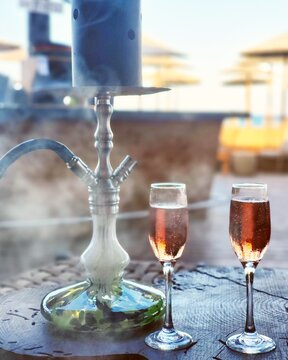 A modern shisha, aka nargile or hookah at a beach bar restaurant in the summer and two glasses of sparkling rose wine on a wooden table with sea background and smoke. A very middle eastern custom
