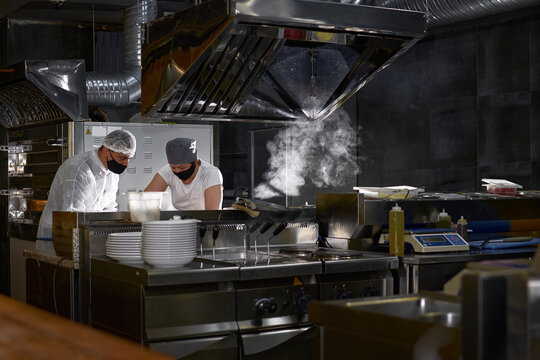 mask on the chef's face in a restaurant: cooks in an open kitchen, a client sees work during a pandemic