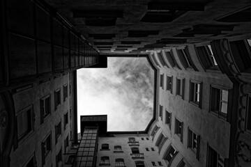 Widok czarno-biały na zachmurzone niebo pośrodku starej kamienicy w Budapeszcie
