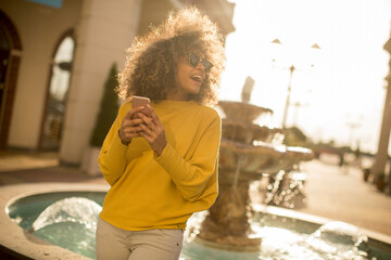 Attractive young woman with curly hair using her touch screen mobile cell phone