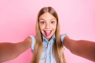 Close up photo of cute playful kid girl blogger grimace face show tongue out make selfie wear denim...