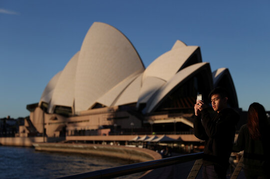 A young man films with his phone in front of the Sydney Opera House in Sydney