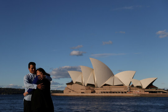 A couple poses for pictures in front of the Sydney Opera House in Sydney