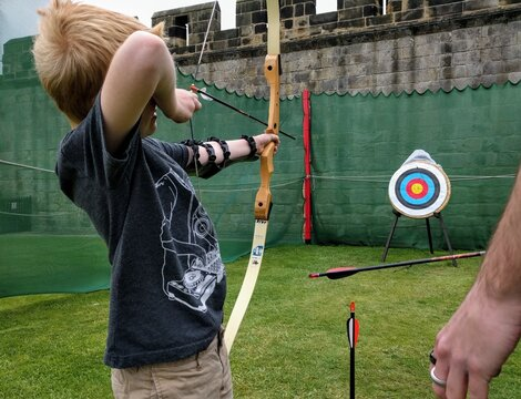 An unidentifiable young man shoots an arrow from a bow into a target at an archery range