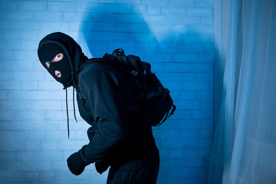 Sneaky scared robber ready to steal something at home