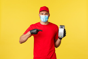 Food delivery, tracking orders, covid-19 and self-quarantine concept. Courier recommends using POS terminal for safe contactless paying during coronavirus pandemic, yellow background
