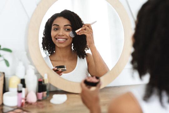 Beautiful black woman applying blush on face, using brush tool, putting makeup