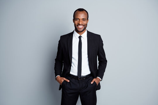 Portrait of his he nice attractive cheerful cheery guy employee banker financier wearing fashionable brandy suit holding hands in pockets posing isolated over grey pastel color background