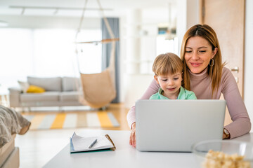 Mother working at home-office with child on her lap