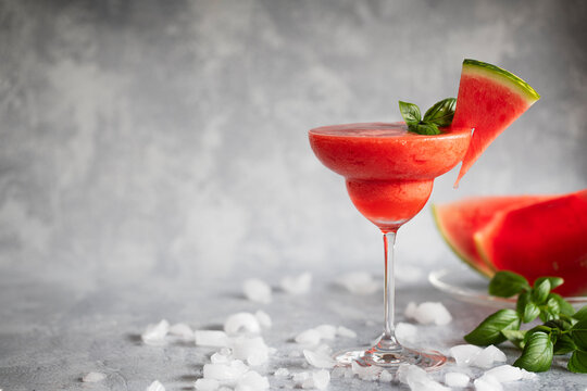 A frozen red drink garnished with watermelon and basil. Frozen margarita.