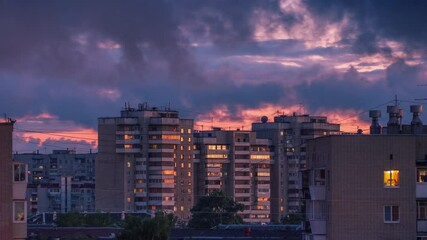 Fotobehang - Storm rainy clouds passing over city skyline as sunset sky reflects in windows of tall apartment buildings in urban area of Yekaterinburg, Russia. Zoom in. Timelapse, 4K UHD.