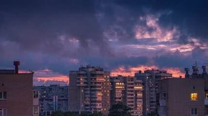 Fotobehang - Epic dramatic colorful storm rainy clouds passing over city skyline as sunset sky reflects in windows of tall apartment buildings in urban area of Yekaterinburg, Russia. Timelapse, 4K UHD.