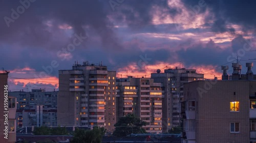 Fotobehang Storm rainy clouds passing over city skyline as sunset sky reflects in windows of tall apartment buildings in urban area of Yekaterinburg, Russia. Zoom in. Timelapse, 4K UHD.