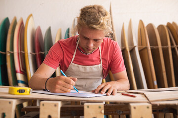 Caucasian male surfboard maker rawing surfboards projects in a sketchbook and making a surfboard