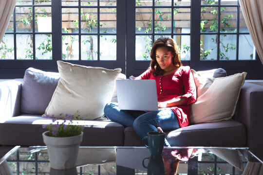 African American woman using a laptop at home during quarantine lock down for coronavirus covid19