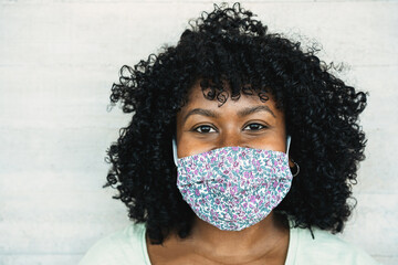 Happy black girl smiling under protective face mask - Young millennial person during coronavirus...