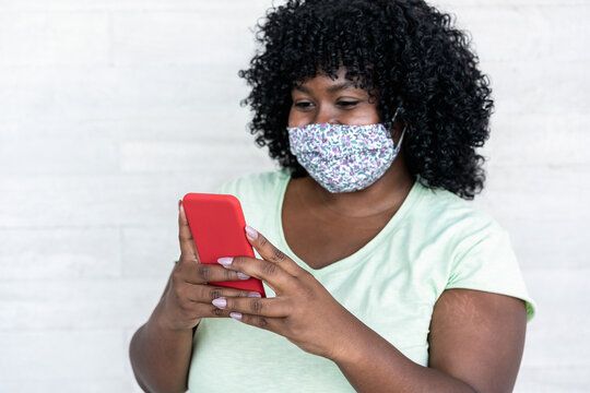 Happy black girl using smartphone outdoor - Young curvy african female having fun watching videos on mobile phone while wearing face protective mask - Coronavirus lifestyle concept - Focus on hands