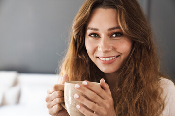 Lovely smiling young girl holding mug
