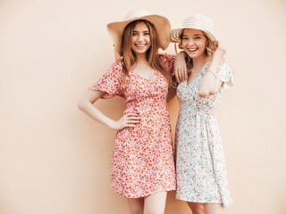 Two young beautiful smiling hipster girls in trendy summer sundress.Sexy carefree women posing on...