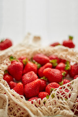 Fresh strawberries in eco-friendly package on white wooden background. Vegetarian organic meal