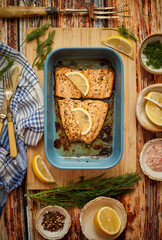 Roasted salmon in heat proof dish. With aromatic dill, lemon, salt and pepper on sides.