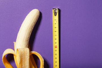 A banana is measured using a yellow ruler on a purple background. Adult material