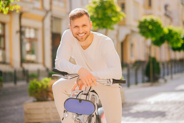 Young successful guy with bicycle leaning hands on the handlebars