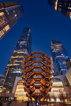 New York City, NY, USA - March 19, 2019: The Vessel (The Hudson Yards Staircase, architect Thomas Heatherwick) at dusk. In the background, 30 Hudson Yards and 10 Hudson Yards skyscrapers,. Manhattan