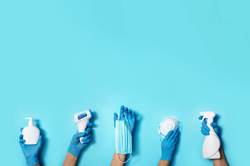 Poster India Raised hands in medical gloves holding masks, sanitizers, soap, non contact thermometer on blue background. Banner. Copy space. Health protection equipment during quarantine Coronavirus pandemic