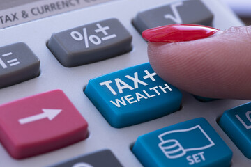 Rich or wealth taxation concept with woman finger pressing tax button of pocket calculator